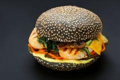 Hamburguer preto com peixes, queijo, salmoura, cenoura, espinafre polvilhado com as sementes de sésamo imagens de stock