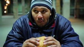 Hamburguer saboroso antropófago desabrigado com fome charity Comida lixo e problemas de saúde vídeos de arquivo