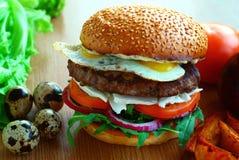 Hamburguer suculento com rissóis de carne, queijo, cebolas, tomates, rúcula, ovos de codorniz Na tabela entre legumes frescos foto de stock