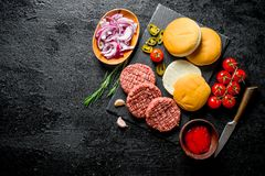 Hamburgueres crus Cozimento de riss?is do hamburguer da carne imagem de stock royalty free