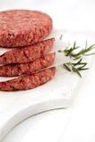 Hamburgueres crus para Hamburger, em uma pilha Fotografia de Stock Royalty Free