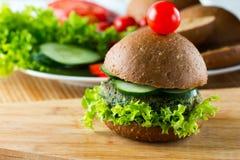 Hamburgueres dos espinafres do vegetariano com pão, pepino e alface de centeio Foto de Stock