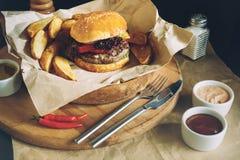 Hamburgueres saborosos frescos com batatas fritas e molho no tampo da mesa de madeira Fotos de Stock
