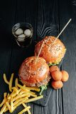 Hamburgueres suculentos caseiros na placa de madeira, bolas do queijo com batatas fritas e vidro da cola imagem de stock