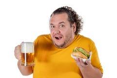 Hamburguesa antropófaga gorda divertida y bebida de consumición del alcohol en el fondo blanco foto de archivo libre de regalías