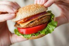 Hamburguesa apetitosa en las manos masculinas Imagen de archivo libre de regalías