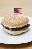 Hamburguesa asada a la parrilla en placa con la bandera americana en superficie de madera Imagenes de archivo