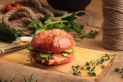 Hamburguesa brillante de moda con los salmones en bollo rosado Fotografía de archivo