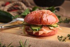 Hamburguesa brillante de moda con los salmones en bollo rosado Imagen de archivo libre de regalías