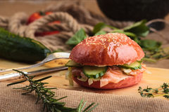 Hamburguesa brillante de moda con los salmones en bollo rosado Foto de archivo