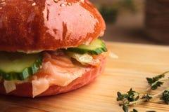 Hamburguesa brillante de moda con los salmones en bollo rosado Fotografía de archivo libre de regalías