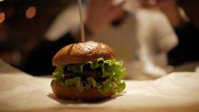Hamburguesa clásica en una tabla en el papel de pergamino Café de los alimentos de preparación rápida almacen de video