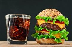 Hamburguesa, cola con hielo en un fondo negro Imagen de archivo