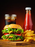 Hamburguesa, cola, patatas fritas y salsa de tomate Fotografía de archivo