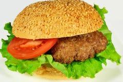 Hamburguesa con carne de vaca, el tomate y el bollo con las semillas de sésamo Imagen de archivo
