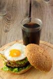 Hamburguesa con el huevo frito y el vidrio de cola Fotos de archivo libres de regalías