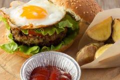 Hamburguesa con el huevo frito y las cuñas asadas de la patata Fotografía de archivo libre de regalías