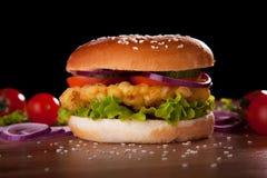Hamburguesa con el pollo, la ensalada, los pepinos, los tomates y las cebollas Foto de archivo