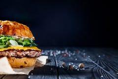 Hamburguesa con la carne, la salsa, la sal y las verduras en el papel del arte fotografía de archivo libre de regalías