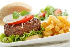 hamburguesa con las fritadas aisladas en blanco Imagen de archivo