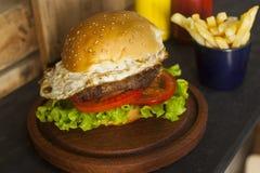 Hamburguesa con las fritadas en la tabla de madera Imagenes de archivo
