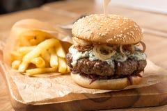 Hamburguesa con las patatas fritas y la salsa Foto de archivo libre de regalías