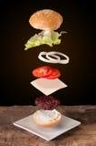 Hamburguesa con los ingredientes del vuelo colocados en tablones de madera Imagen de archivo libre de regalías