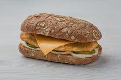Hamburguesa con los pescados, el pepino conservado en vinagre y el queso en el backgroud blanco Foto de archivo libre de regalías