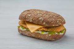 Hamburguesa con los pescados, el pepino conservado en vinagre y el queso en el backgroud blanco Imágenes de archivo libres de regalías