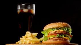 Hamburguesa con patatas fritas y un vidrio con cola del hielo en un fondo rústico negro almacen de video