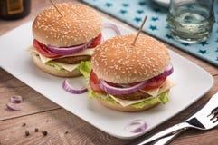 Hamburguesa con queso doble, cebollas rojas y tomates en una placa con las estrellas blancas imagen de archivo libre de regalías
