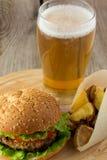 Hamburguesa, cuñas asadas de la patata y vidrio de cerveza Imagenes de archivo