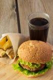 Hamburguesa, cuñas de la patata y cola en la placa de madera Foto de archivo