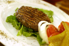 Hamburguesa de la carne asada en plato blanco grande imagen de archivo libre de regalías
