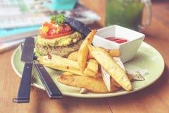 Hamburguesa del carbón de leña con la patata y las cuñas Fotografía de archivo libre de regalías