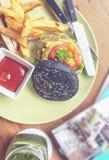 Hamburguesa del carbón de leña con la patata y las cuñas Foto de archivo libre de regalías