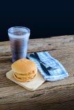 Hamburguesa del pollo y vidrio de cola en tabla de cortar de madera con Foto de archivo