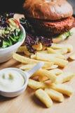 Hamburguesa del vegano con la ensalada, y las patatas fritas fotos de archivo libres de regalías