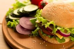 Hamburguesa del vegano con las verduras, las setas y la ensalada apiladas en una tabla de cortar foto de archivo libre de regalías