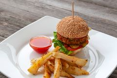 Hamburguesa del vegano, ingredientes: bollo del sésamo, Patty de garbanzos, chile fotos de archivo