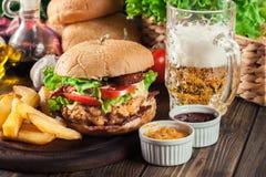 Hamburguesa deliciosa con el pollo, el tocino, el tomate y el queso Foto de archivo