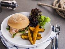 Hamburguesa deliciosa con una empanada jugosa del cerdo con las fritadas en la placa blanca Fotografía de archivo