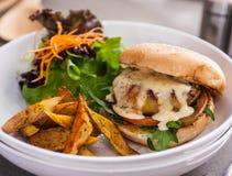 Hamburguesa deliciosa con una empanada jugosa del cerdo con las fritadas en la placa blanca Foto de archivo