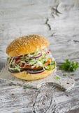 Hamburguesa deliciosa del veggie con la col, el tomate, el pepino, las cebollas y las pimientas en una superficie de madera liger Foto de archivo