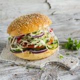 Hamburguesa deliciosa del veggie con la col, el tomate, el pepino, las cebollas y las pimientas en una superficie de madera liger Fotos de archivo