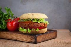 Hamburguesa fresca del vegano con la chuleta del tomate, del pepino, de la lechuga y del vegano en el tablero de madera foto de archivo libre de regalías