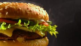 Hamburguesa fresca deliciosa gigante que gira en fondo oscuro del humo Opinión macra del cheeseburger Comida rápida americana, ma metrajes