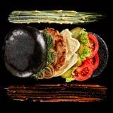 Hamburguesa fresca grande con la salsa en la placa negra en fondo de madera fotografía de archivo libre de regalías