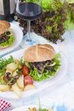 Hamburguesa grande con la ensalada y las patatas Un vidrio de vino rojo Cena sabrosa Junk Food texto Copie el espacio fotografía de archivo libre de regalías
