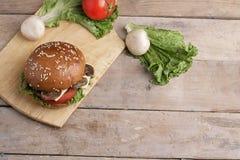 Hamburguesa grande con las hojas de las setas, del tomate y de la ensalada, lugar para el texto foto de archivo libre de regalías